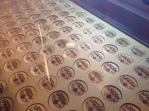 Laser cutting wooden doubloons for Mardi Gras throws